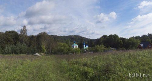 Мальский монастырь находится внизу, около озера, с дороги видны только верхушки его храмов